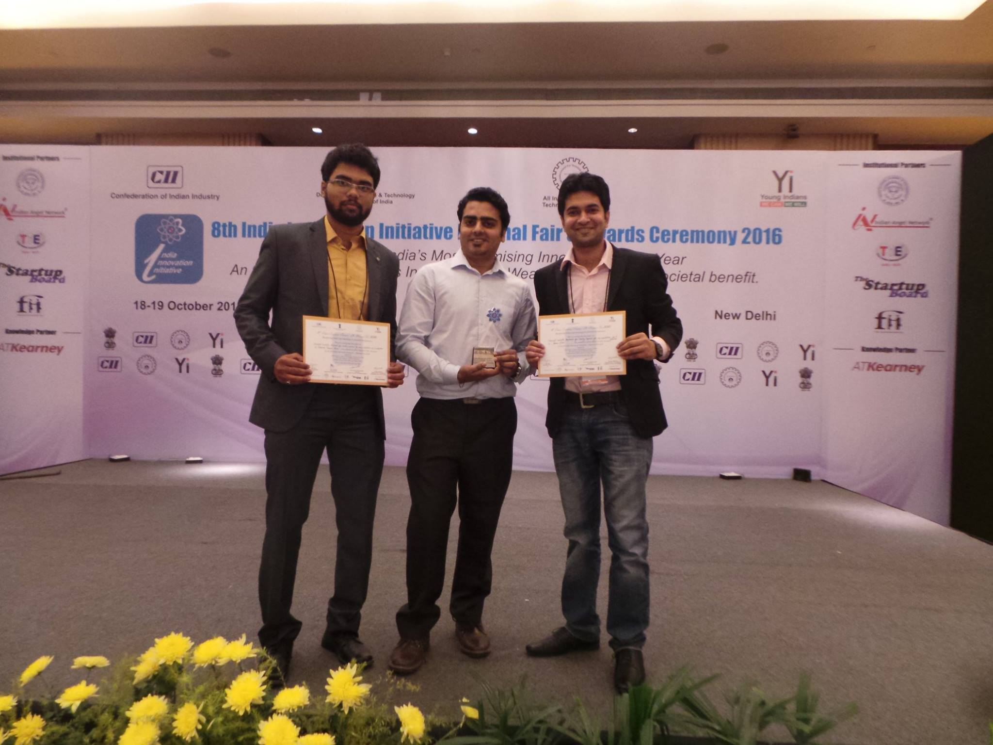 From left to Right Shaswat, Vaibhav and Gaurav posing on stage with Sliver Award for Best Innovators of 2016